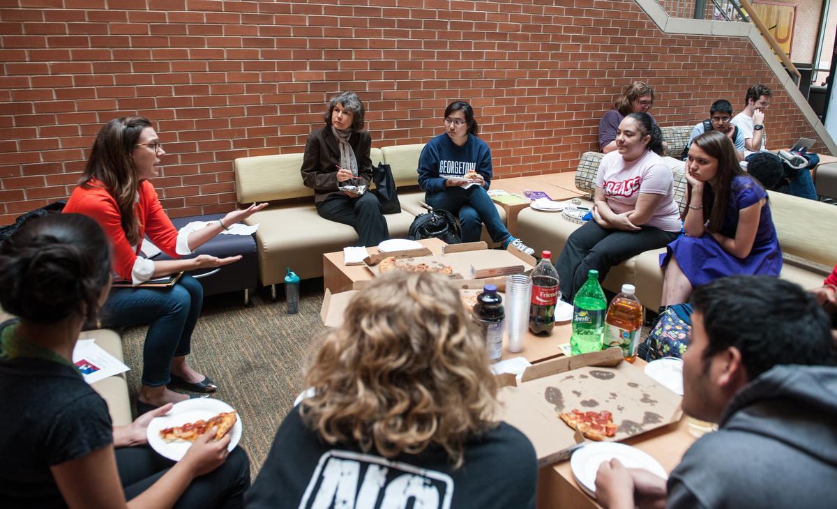 Students talking to faculty while eating pizza.