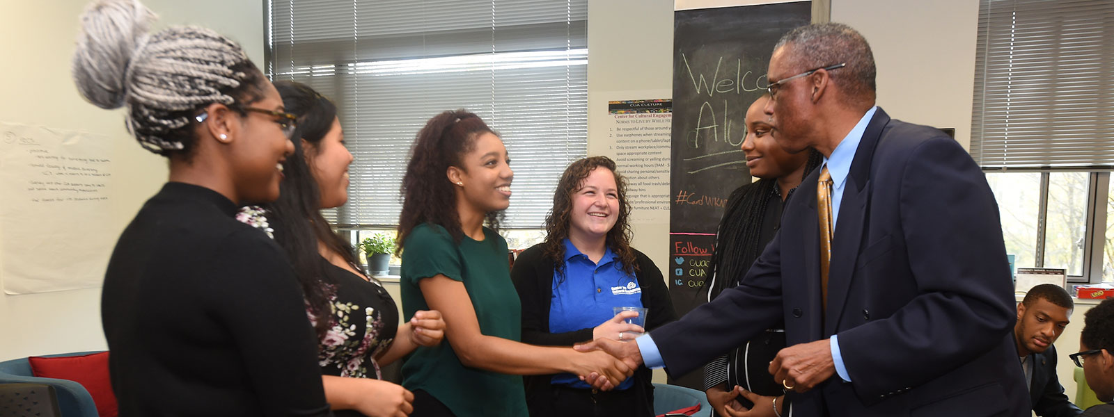 Students smiling and shaking hands with administrator