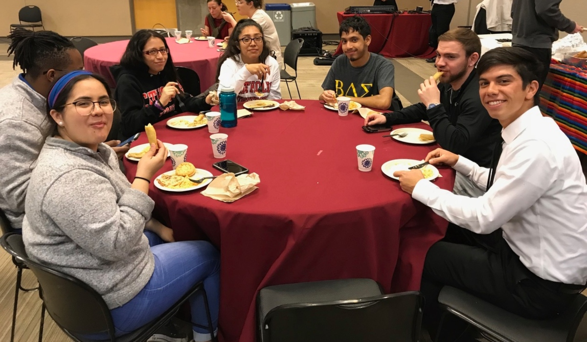 Students sitting at table, eating, and smiling