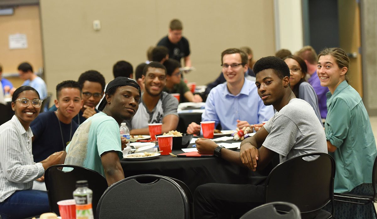 Diverse group of students sitting at a table and smiling